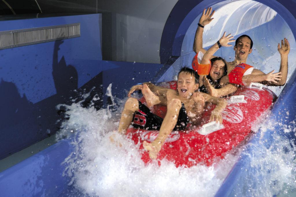 personnes sur bouée rouge dans toboggan et eau