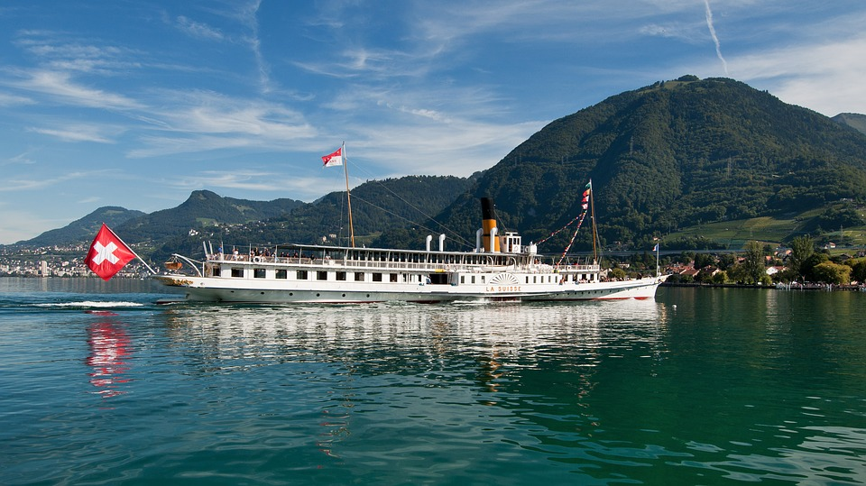 bateau sur lac avec drapeau suisse et montagne