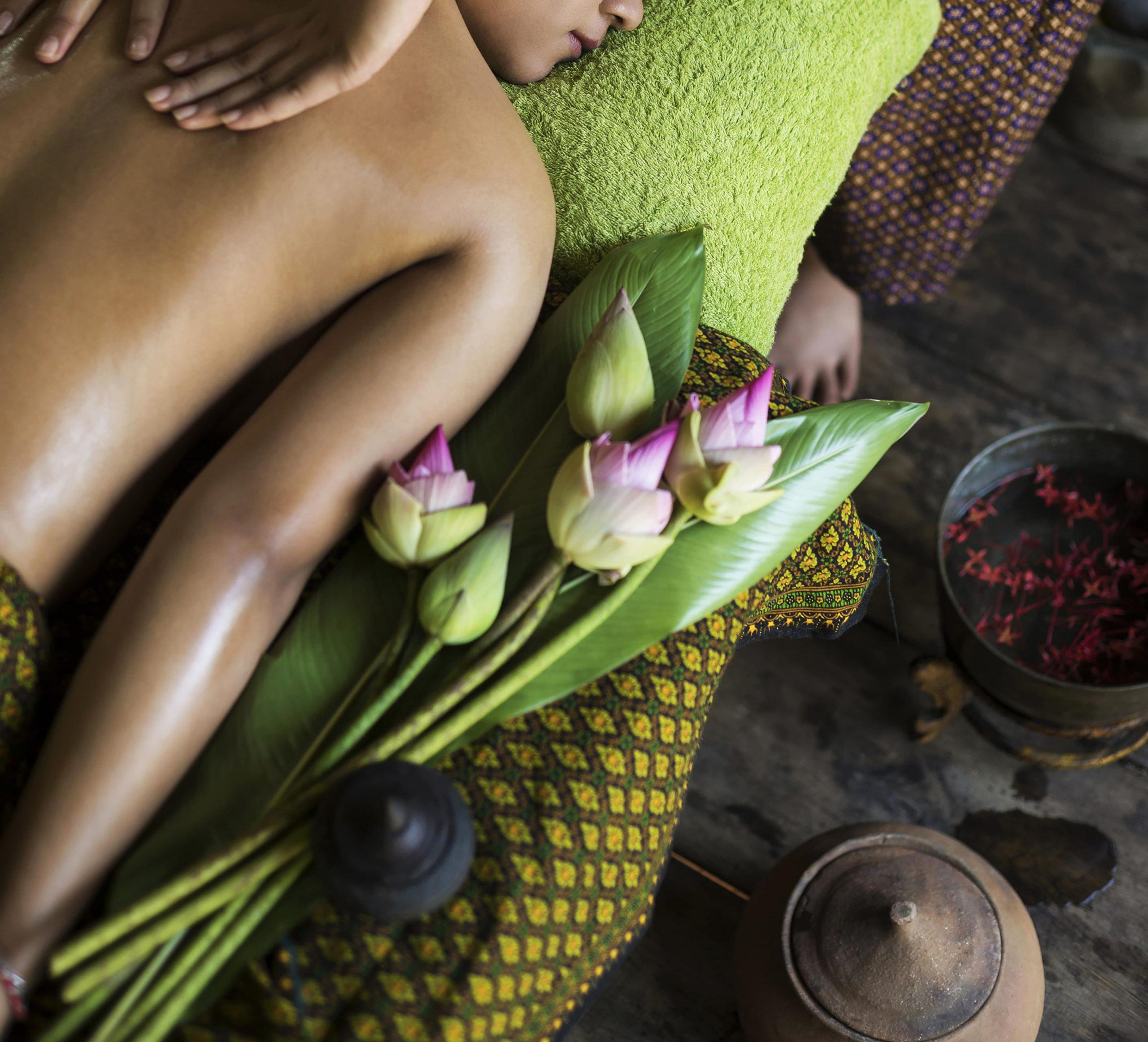 femme allongée avec mains de massage sur dos et fleurs de lotus